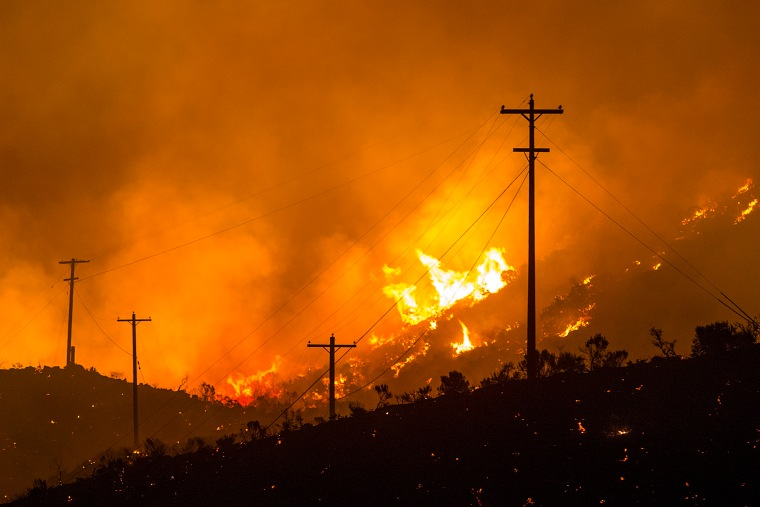 Flames wrap around the base of telephone poles during a wildfire near Rock Island Grade in Crescent Bar, Washington on Friday, June 24, 2016.