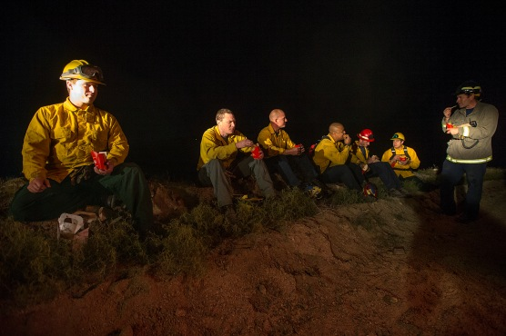 Fire crews from Chelan and Douglas County Fire Districts take a quick break to hydrate and eat after extinguishing a wildfire near Rock Island, Washington on Friday, June 24.