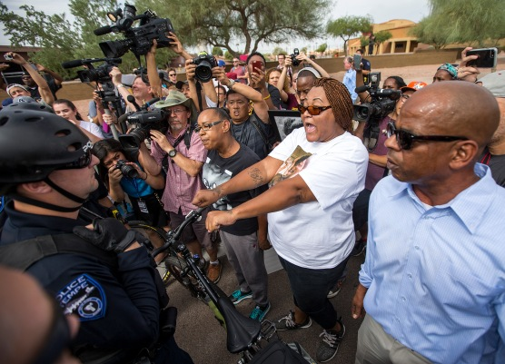 Sarah Coleman, center in white, holds out her hands, asking to be arrested, during a police-violence protest on the Mill Avenue Bridge on Monday, Sept. 26, 2016 in Tempe, Arizona. Coleman's son, Dalvin Hollins, died in an incident with local police in July.