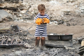 A young child, whose parents wished to stay anonymous, looks through the rubble of his home after the Carlton Complex Megafire swept through Pateroes, Washington in the summer of 2014.