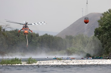 The bucket from a helicopter, upper right, leaks a spray of water onto watching inner-tubers as another helicopter approaches the surface of the Wenatchee River on Sunday, June 28, 2015. The crews worked to control the Sleepy Hollow Fire in Wenatchee, Washington for over a week.