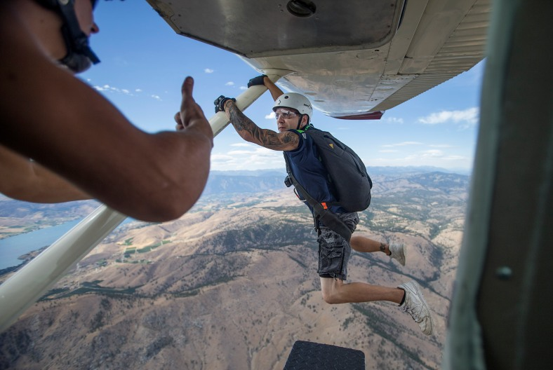 Skydive Chelan instructor Buck Prib, left, gives the OK signal for student Andrew Paton, of Wenatchee, to drop from the plane on a skydiving trip over Chelan, Washington on Sunday, August 9, 2015.