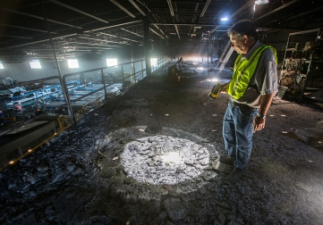 Larry Blakey, the facility and food safety director for Bluebird Growers, looks down at rebar sticking up through the floor of an organic cherry line on Tuesday, July 28, 2015, in Wenatchee, Washington. The Sleepy Hollow Fire ignited this area of Bluebird's organic cherry packing line.