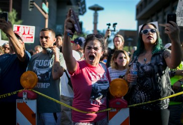 Lieve Snellen, of Phoenix, yells at opposing demonstrators on Tuesday, August 22, 2017. Snellen said she moved to the United States from West Africa when she was 12. She said she believes America is built on immigration and stands against Trump's politics.