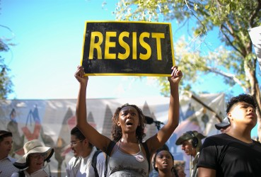 "Chitara Smith, of Chandler, Arizona, holds a ""resist"" sign outside President Donald Trump's rally on Tuesday, August 22, 2017."