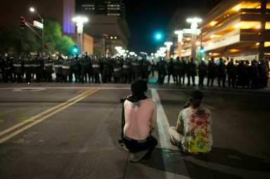 Protestors sit in front of gathered police officers after a campaign rally featuring President Donald Trump's rally in Phoenix on August 22, 2017.