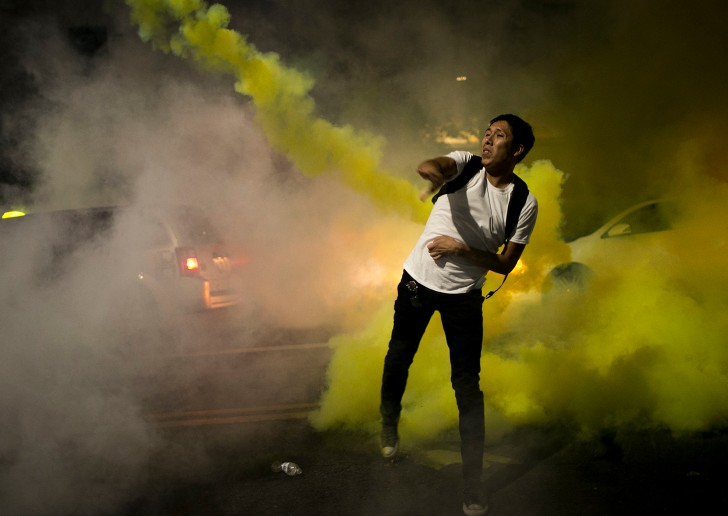 A protestor throws a tear gas canister back toward riot police outside President Donald Trump's rally in Phoenix on August 22, 2017.