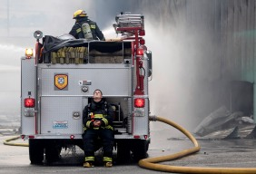 Firefighter John Bussel, of Douglas County Fire Department's No. 2 station, takes a moment to rest his eyes while crews continue to battle a warehouse blaze on Wenatchee Avenue in Wenatchee, Washington on Monday, June 29, 2015.