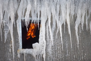 With temperatures in the low single digits, water used by the firefighters quickly froze on the building as flames continued to burn inside on Monday. The building, a Blue Bird warehouse, caught fire Sunday night in Peshastin.