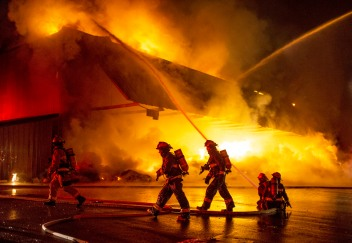 Firefighters deploy hoses to combat a fully involved commercial fire at a Blue Bird warehouse in Peshastin on Sunday. The building was a total loss.